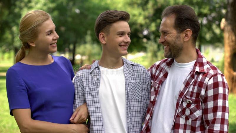 Padres felices que miran al hijo adolescente con orgullo, estudiante universitario acertado imagen de archivo libre de regalías