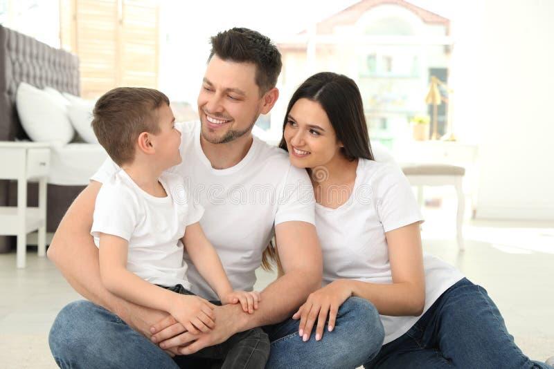 Padres felices y su hijo que se sientan junto en piso Tiempo de la familia imagenes de archivo