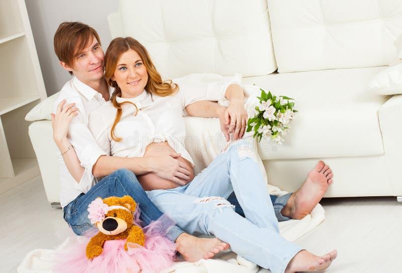 Padres futuros felices que se sientan junto cerca del sofá blanco foto de archivo libre de regalías
