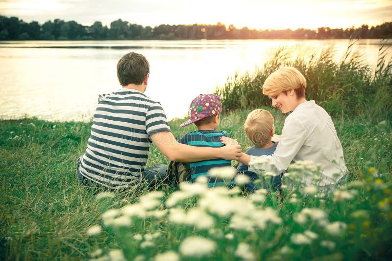 Padres hermosos jovenes que abrazan a sus hijos jovenes en la puesta del sol cerca del lago Familia que camina a lo largo del río imagen de archivo