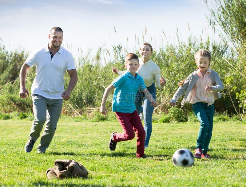 Padres jovenes con dos niños que juegan a fútbol imagenes de archivo