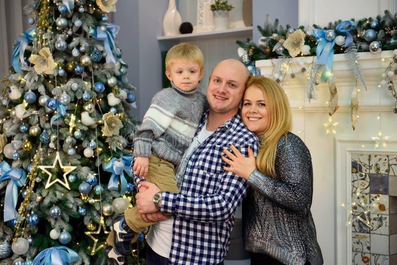 Padres jovenes con su hijo que sonríe en la cámara mientras que celebra la Navidad en casa foto de archivo