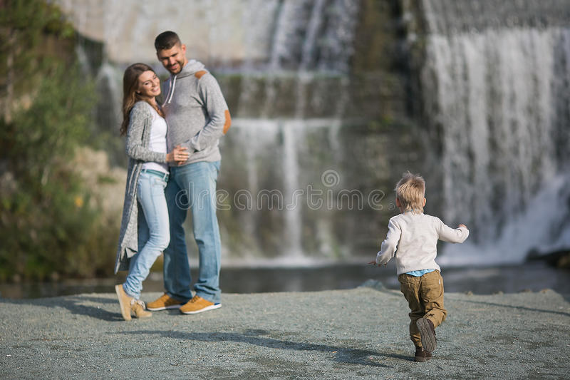 Padres jovenes felices y su hijo cerca de una cascada imagenes de archivo
