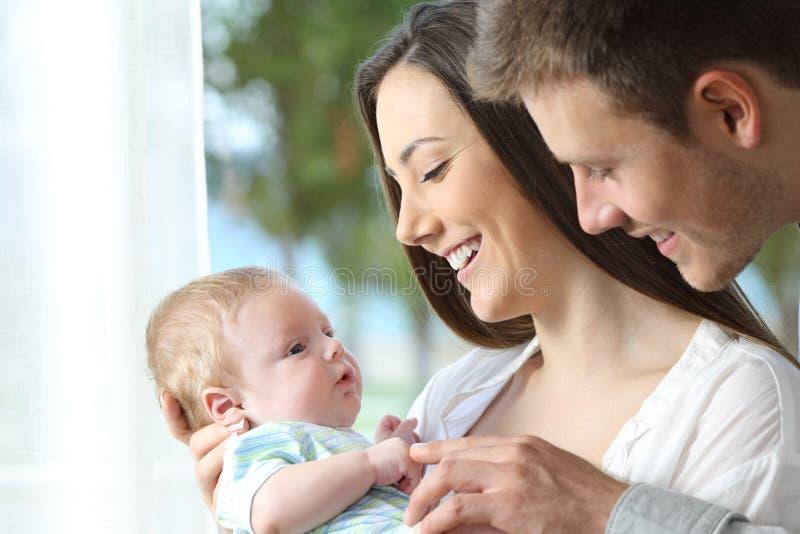 Padres orgullosos que juegan con su bebé fotos de archivo