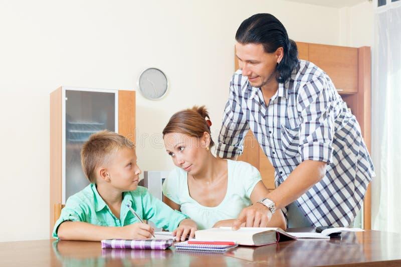Padres que ayudan a adolescente con la preparación imagenes de archivo