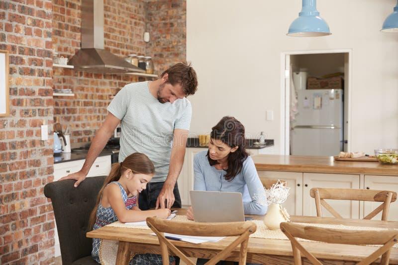 Padres que ayudan a la hija con la preparación en la tabla de cocina fotos de archivo