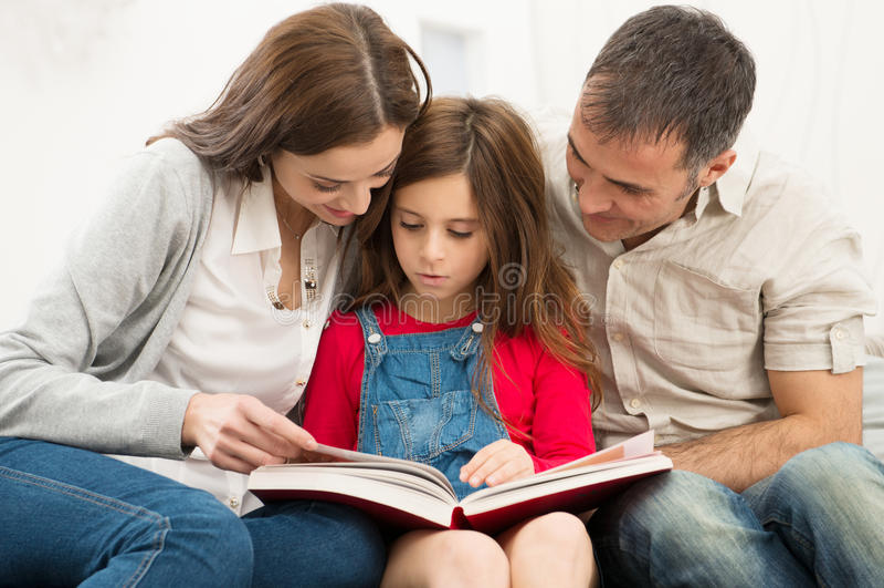 Padres que ayudan a la hija en estudios imagen de archivo