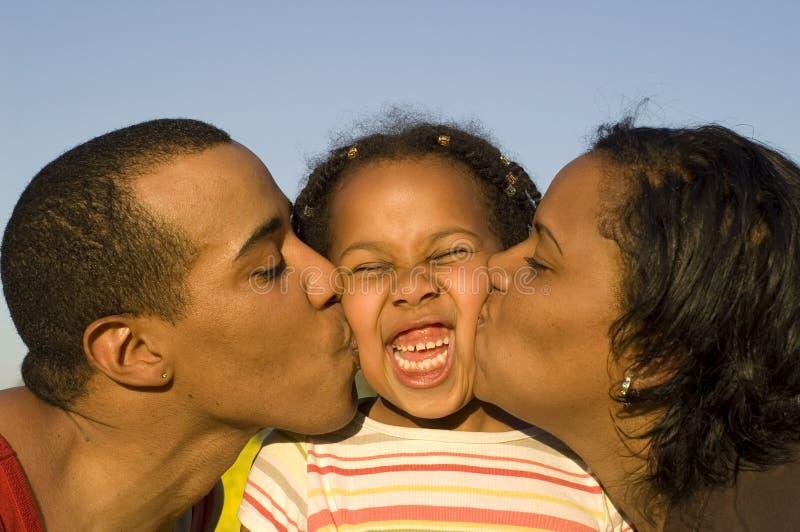 Padres que besan a la hija fotos de archivo libres de regalías