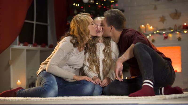 Padres que besan a la hija adorable debajo del árbol de navidad, junto el días de fiesta imagenes de archivo