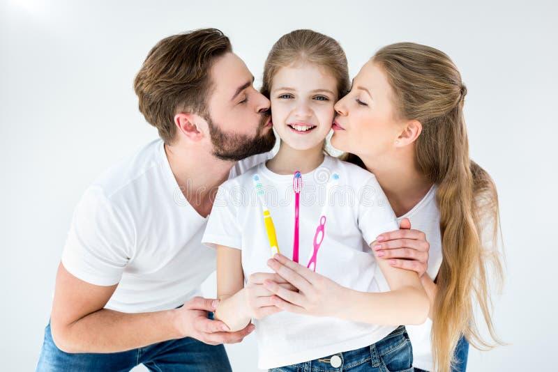 Padres que besan a la pequeña hija linda que sostiene los cepillos de dientes fotografía de archivo libre de regalías