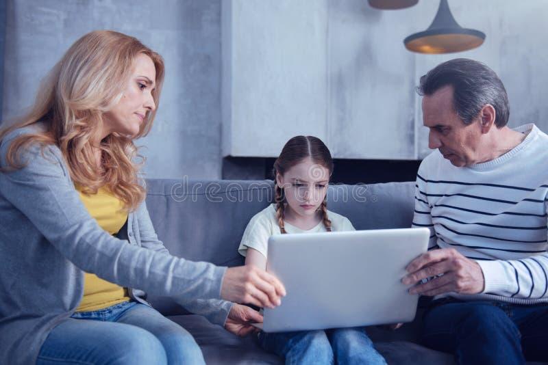 Padres que cuidan agradables que se sientan alrededor de su hija imagen de archivo libre de regalías