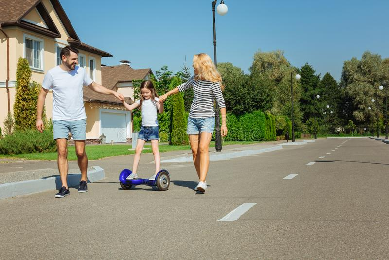 Padres que cuidan que enseñan a la hija a montar hoverboard fotos de archivo libres de regalías