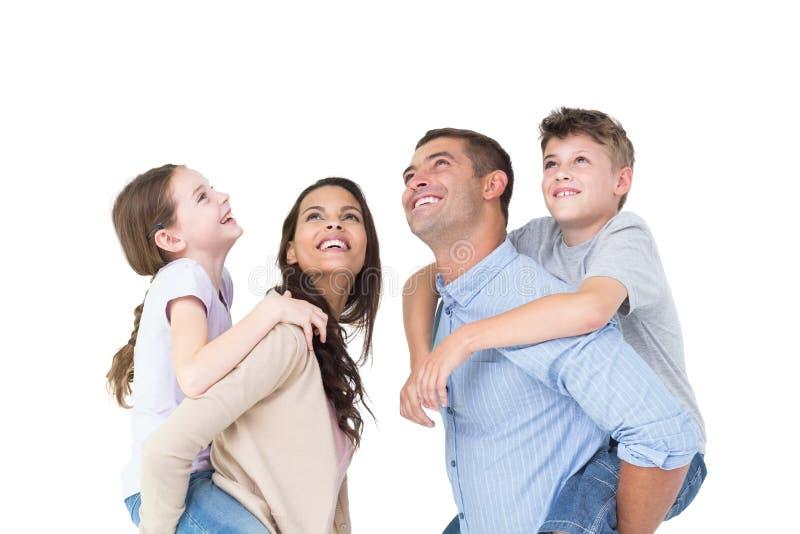 Padres que dan a cuestas paseo a los niños mientras que mira para arriba imagenes de archivo