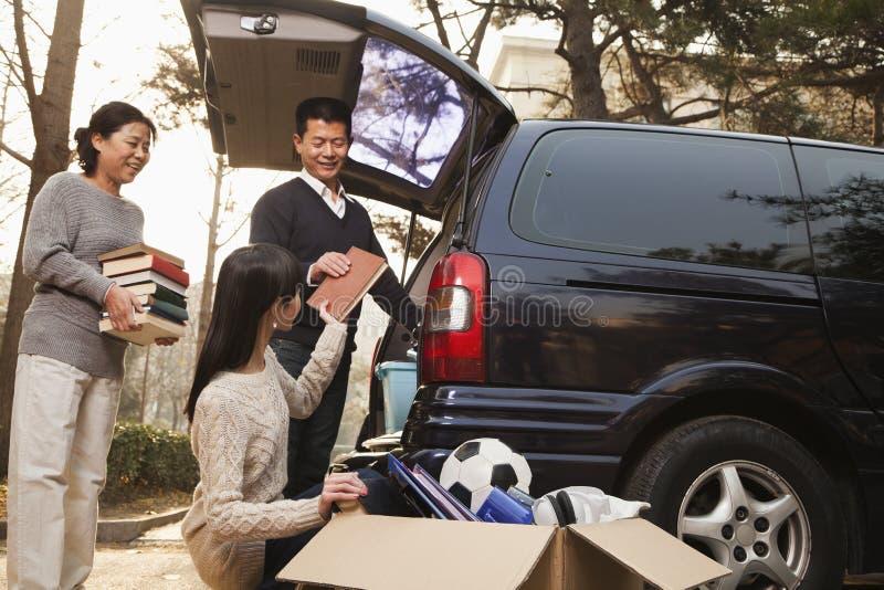 Padres que desempaquetan el coche para un movimiento a la universidad, Pekín foto de archivo libre de regalías