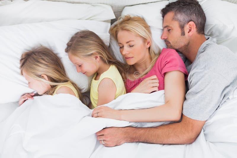 Padres que duermen en cama con sus gemelos imagenes de archivo