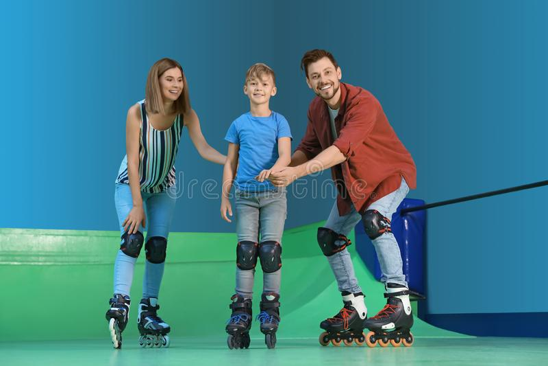 Padres que enseñan a su patinaje sobre ruedas del hijo imagenes de archivo
