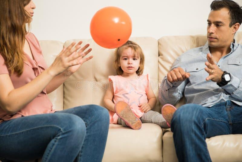 Padres que intentan parar a su hija del griterío imagen de archivo libre de regalías