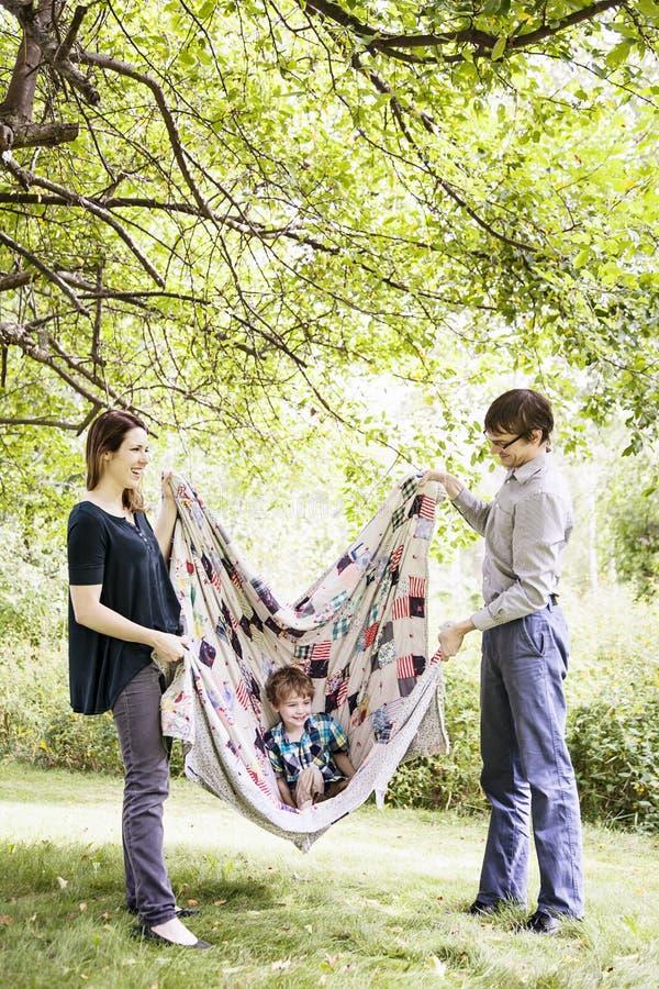 Padres que juegan con el niño en manta imágenes de archivo libres de regalías