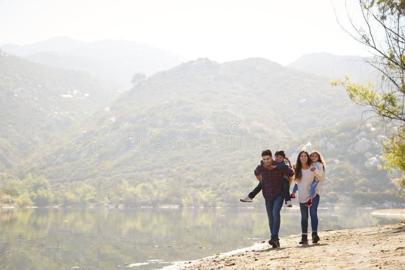 Padres que llevan a cuestas a sus niños jovenes por un lago de la montaña fotos de archivo libres de regalías