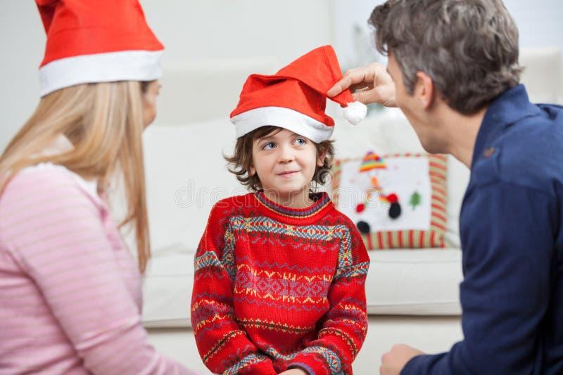 Padres que miran al hijo que lleva a Santa Hat imagenes de archivo