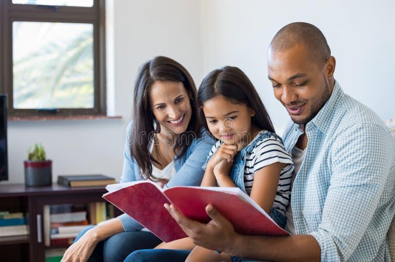 Padres que miran el libro de ejercicio de la hija imagen de archivo libre de regalías