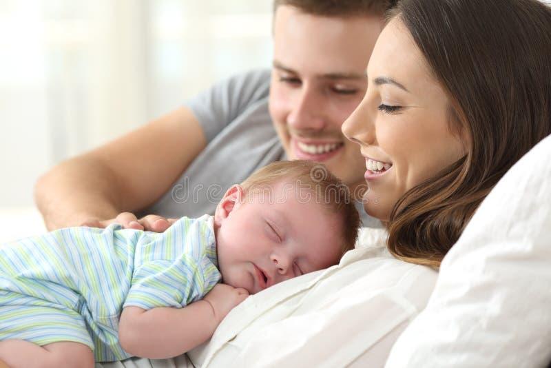 Padres que miran su dormir del bebé imagen de archivo