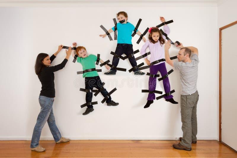 Padres que pegan a niños a la broma de la pared