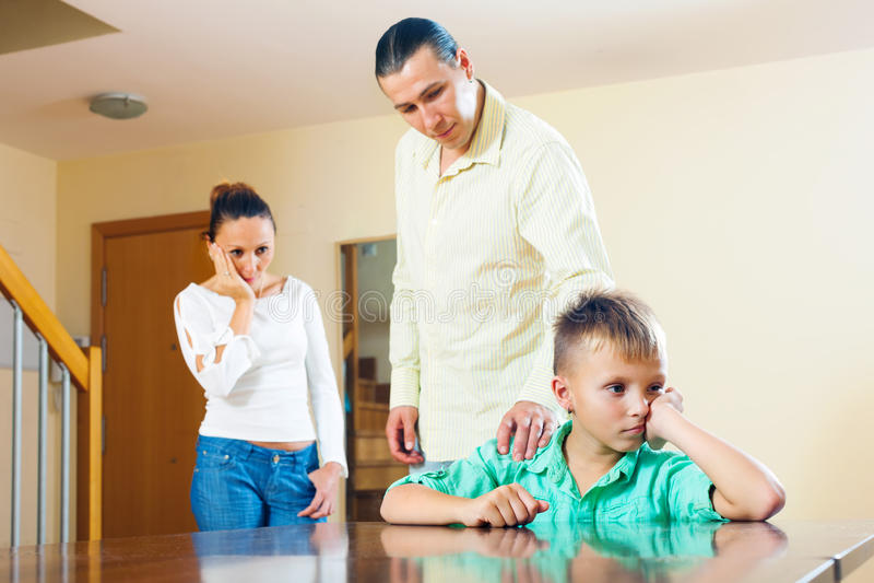 Padres que regañan al hijo del adolescente. Foco en muchacho solamente foto de archivo