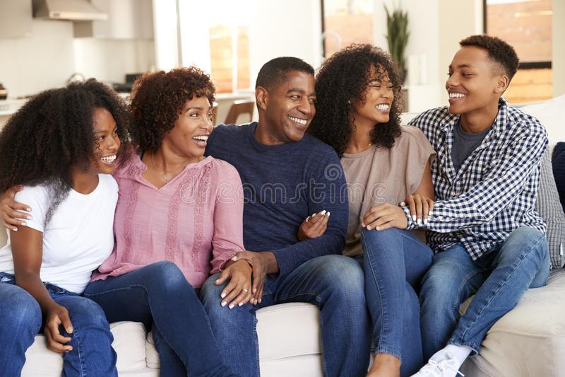 Padres que se relajan en casa con su adolescencia y niños adultos jovenes imagen de archivo libre de regalías