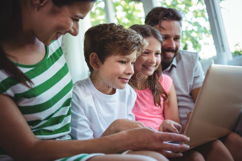Padres que se sientan en el sofá con sus niños y que usan el ordenador portátil en sala de estar fotografía de archivo libre de regalías