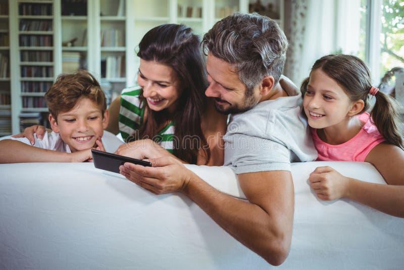 Padres que se sientan en el sofá con sus niños y que usan el teléfono móvil en sala de estar foto de archivo libre de regalías