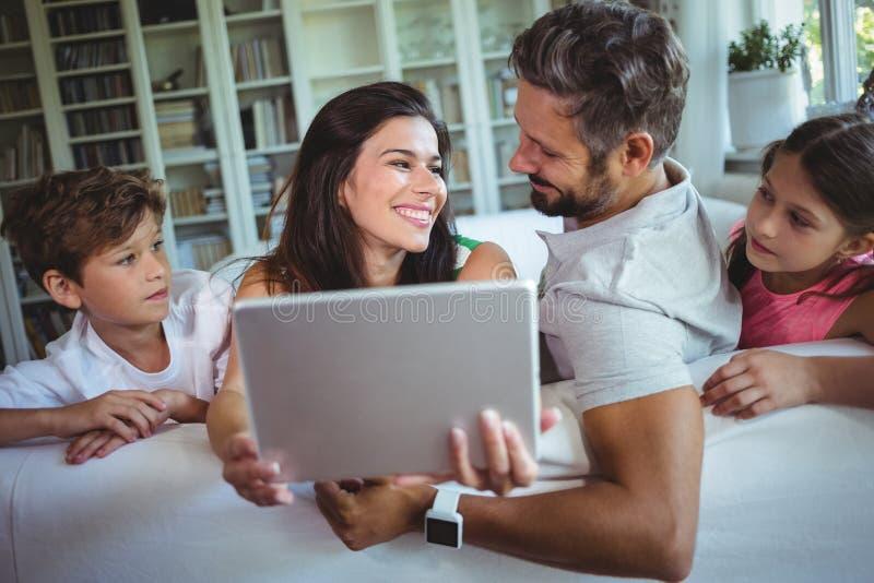 Padres que se sientan en el sofá con sus niños y que usan la tableta digital en sala de estar foto de archivo libre de regalías