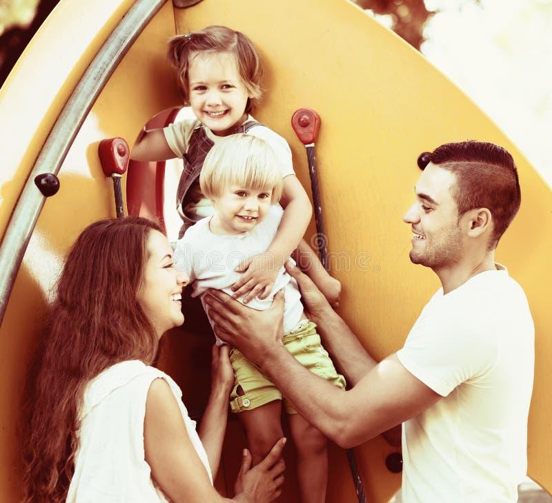 Padres sonrientes que ayudan a niños en las escaleras imagenes de archivo