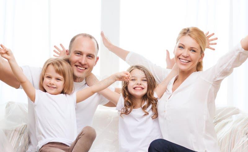 Padres sonrientes y dos niñas en el nuevo hogar imagen de archivo libre de regalías