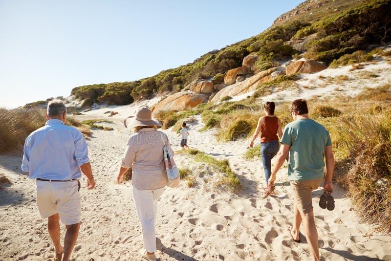 Padres y abuelos que caminan en la playa con el muchacho joven que corre delante de ellos foto de archivo