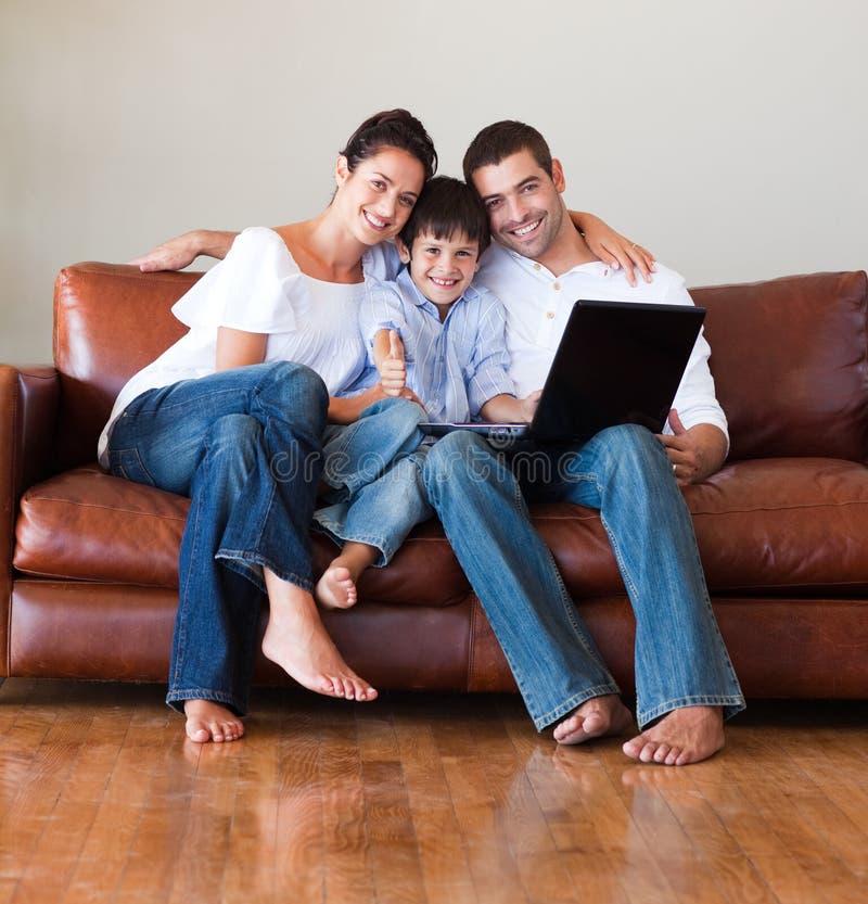 Padres y cabrito usando una computadora portátil con los pulgares para arriba fotos de archivo