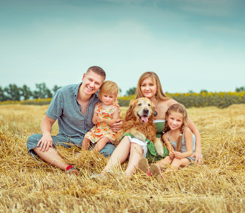 Padres y dos hijas con el perro fotos de archivo