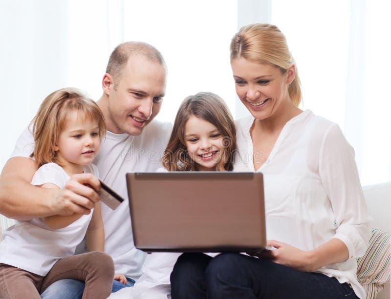 Padres y dos muchachas con el ordenador portátil y la tarjeta de crédito fotografía de archivo libre de regalías