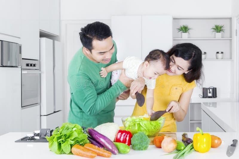 Padres y niña que hacen la ensalada imagen de archivo