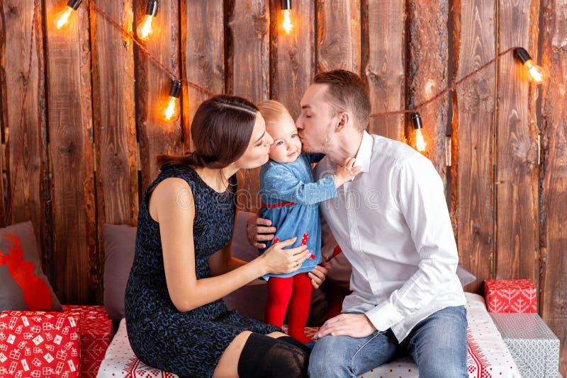 Padres y niño que se divierten en el sitio del desván-estilo, fondo rústico de madera con una guirnalda de bulbos Familia cariños foto de archivo
