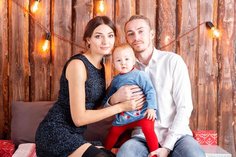 Padres y niño que se divierten en el sitio del desván-estilo, fondo rústico de madera con una guirnalda de bulbos Familia cariños fotos de archivo libres de regalías