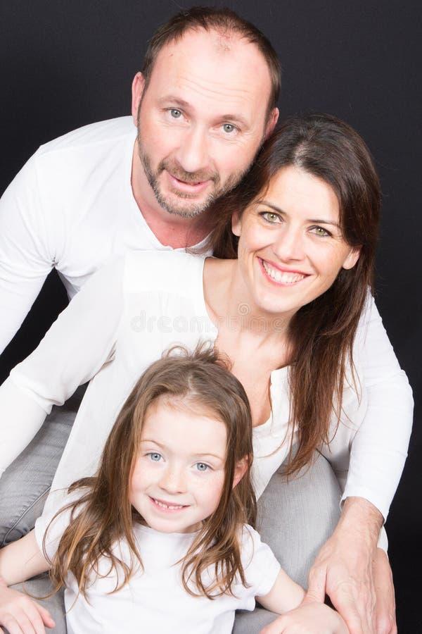 Padres y niño que se relajan en casa en el sofá imágenes de archivo libres de regalías