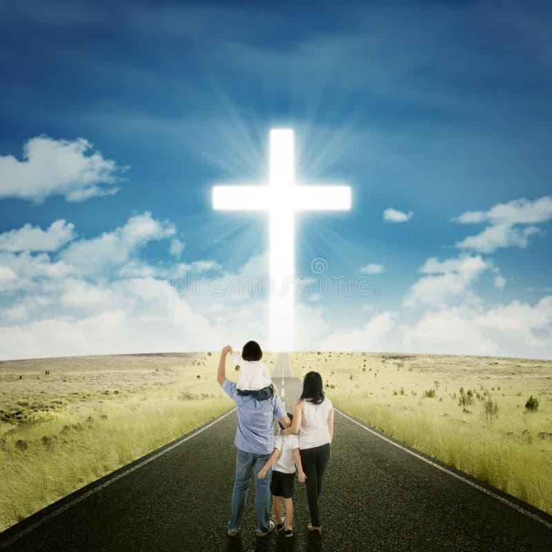 Padres y niños en el camino con una cruz fotos de archivo