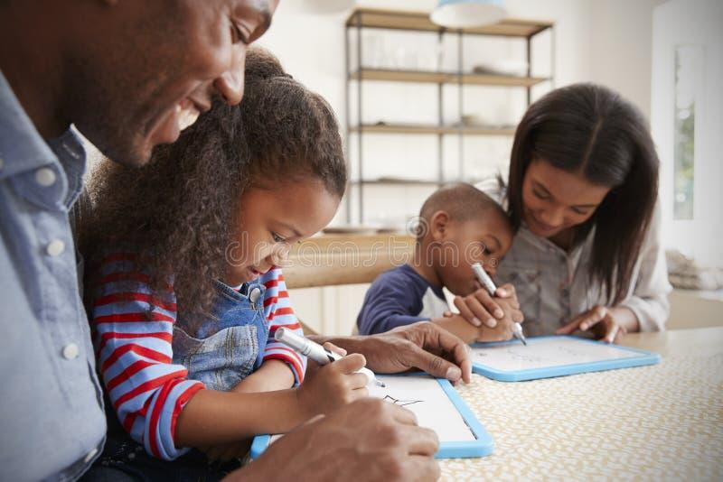 Padres y niños que dibujan en Whiteboards en la tabla imagenes de archivo