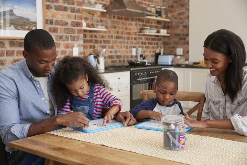 Padres y niños que dibujan en Whiteboards en la tabla foto de archivo libre de regalías