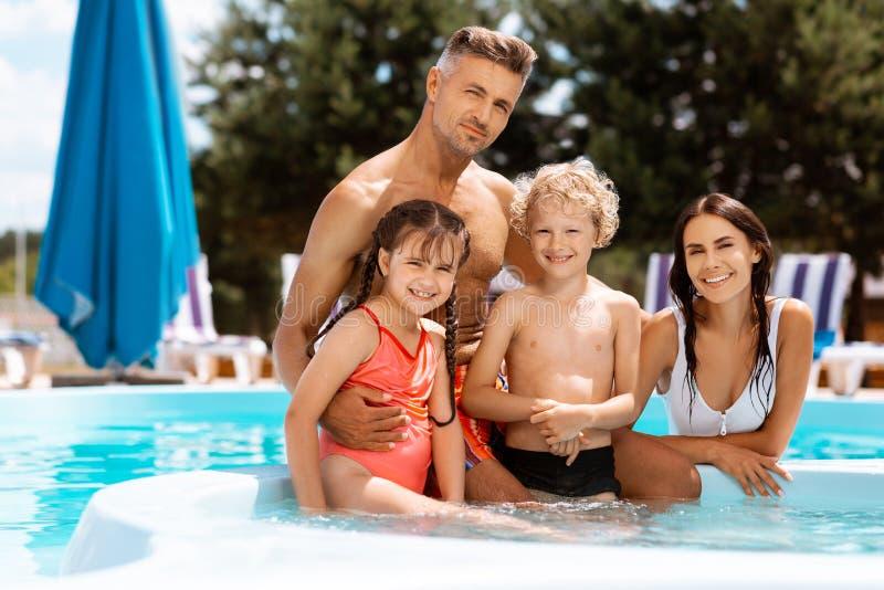 Padres y niños que disfrutan de vacaciones en piscina junto foto de archivo