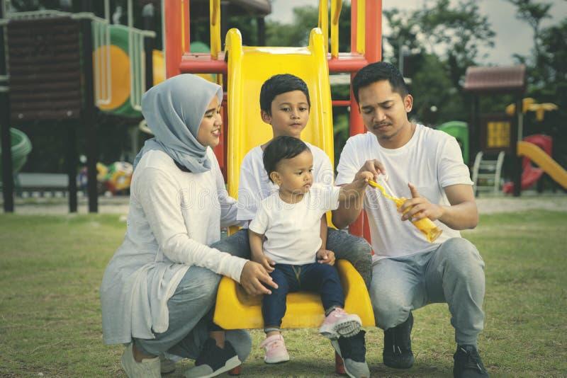Padres y niños que juegan burbujas de jabón en parque foto de archivo libre de regalías