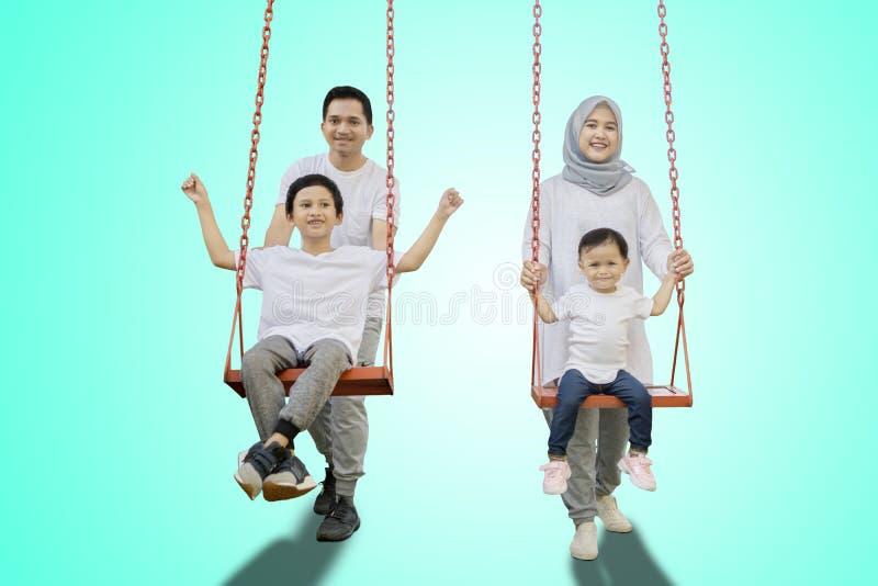 Padres y niños que juegan con los oscilaciones fotografía de archivo