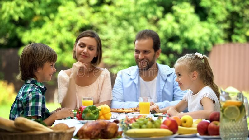 Padres y niños que se sientan en la tabla, disfrutando de la cena de la familia, divirtiéndose, alegría imagen de archivo