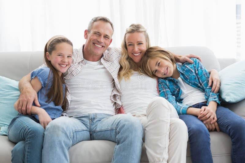 Padres y niños que se sientan junto en el sofá imagen de archivo libre de regalías